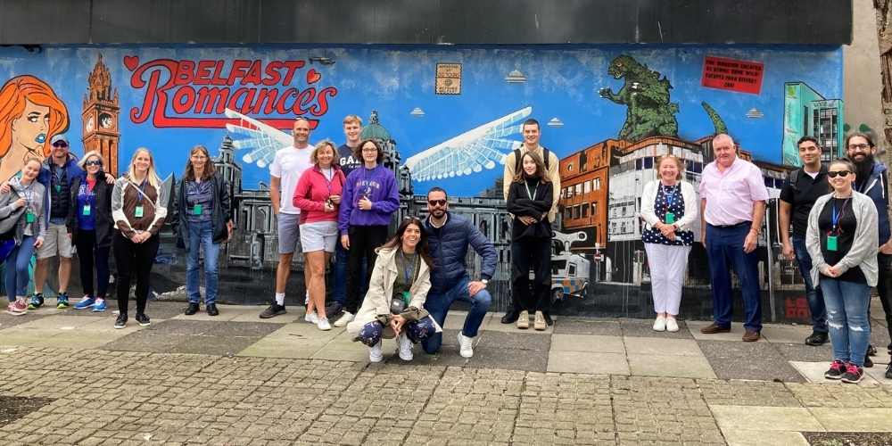 Visitors in front of the Belfast Romances mural
